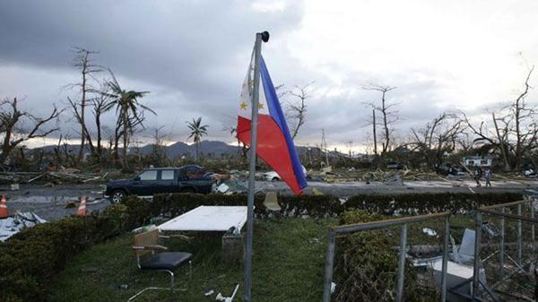 A Philippine flag flutters amidst the devastation brought about by powerful Typhoon Haiyan at Tacloban city, in Leyte province, central Philippines.