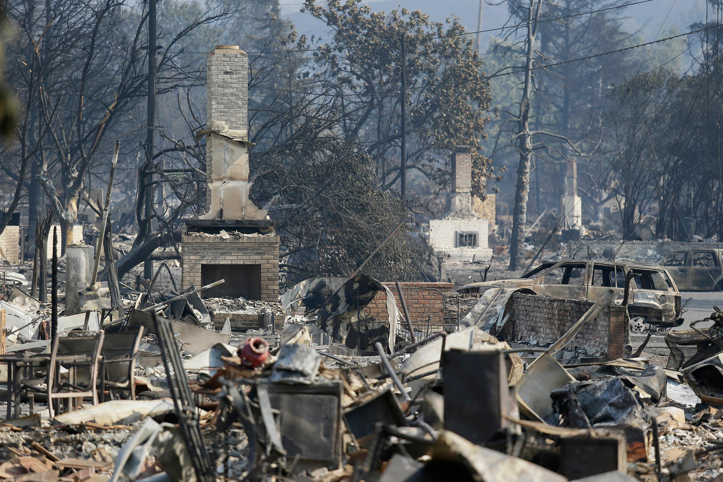 A row of chimneys stand in a wildfire-damaged neighborhood along Mark West Springs Road, Wednesday, Oct. 11, 2017, in Santa Rosa, Calif. Officials say they have thousands of firefighters battling 22 blazes burning in Northern California and that more are coming from nearby states. (AP Photo/Eric Risberg)