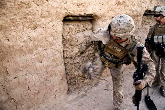 U.S. Marine Corps Cpl. Jarrett Goff kicks a wall in an empty compound during a patrol in Washir village in Helmand province, Afghanistan, July 29, 2013. Goff, a team leader, is assigned to Fox Company, 2nd Battalion, 2nd Marine Regiment.