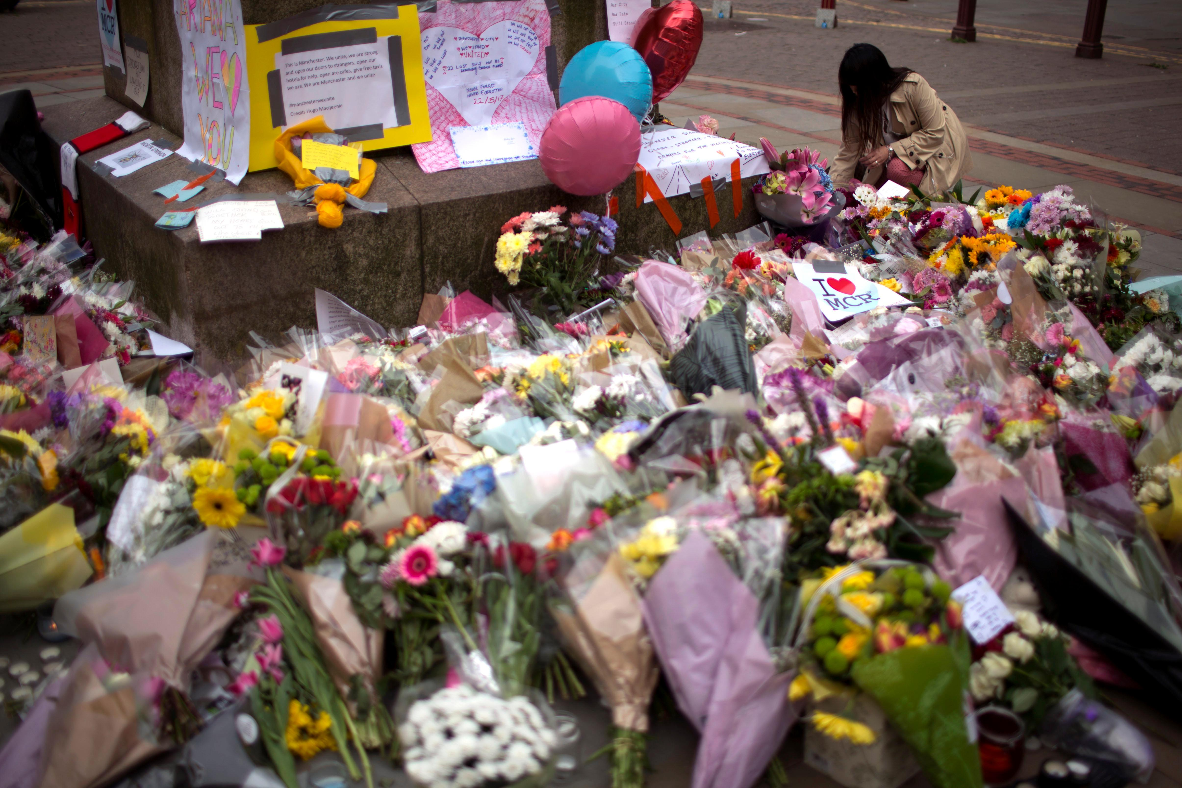 A woman places flowers at a memorial for the victims of a suicide attack at a concert by Ariana Grande that killed more than 20 people Monday night in central Manchester, Britain, Wednesday, May 24, 2017. (AP Photo/Emilio Morenatti)