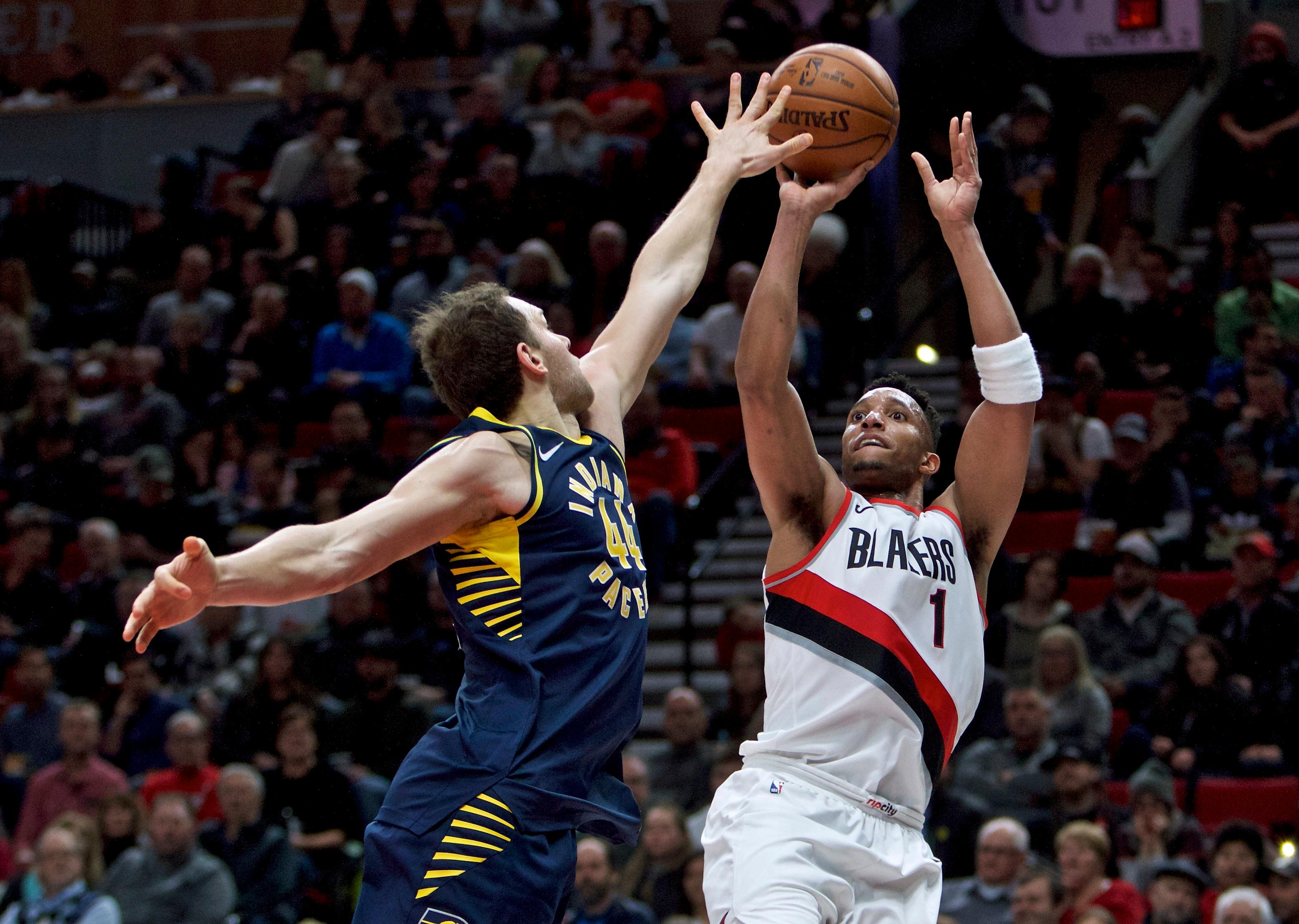 Portland Trail Blazers guard Evan Turner, right, shoots over Indiana Pacers forward Bojan Bogdanovic during the second half of an NBA basketball game in Portland, Ore., Thursday, Jan. 18, 2018. (AP Photo/Craig Mitchelldyer)