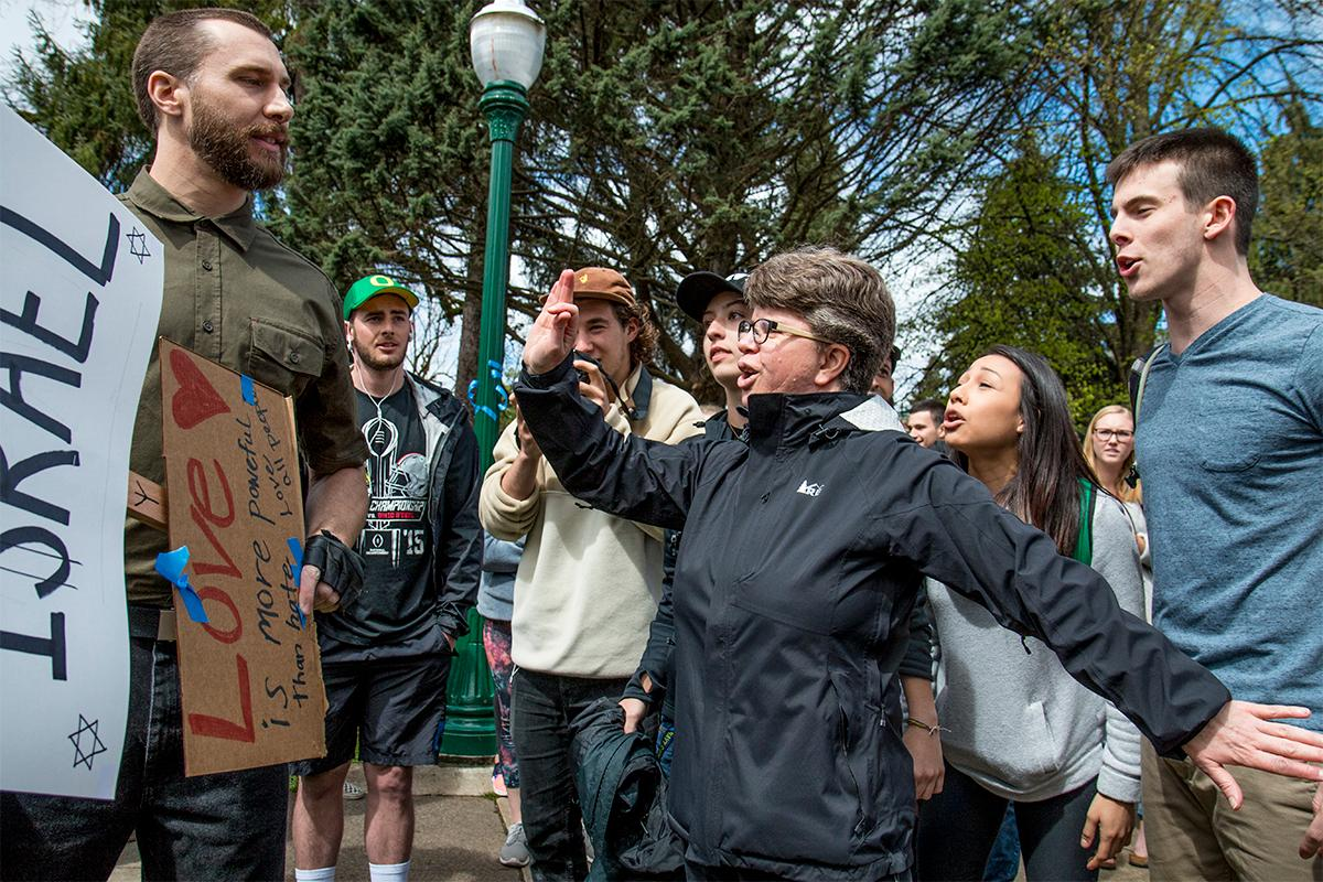 "Neo-Nazis momentarily caused a stir outside the EMU on the University of Oregon campus. According to a man in the crowd they were promoting a holocaust denial film. While some UO students engaged in debate with the two men, others shouted at them to ""go home,"" and that they ""didn't want them here."" The two men soon drove away in their car to the applause of the crowd. Photo by August Frank, Oregon News Lab"