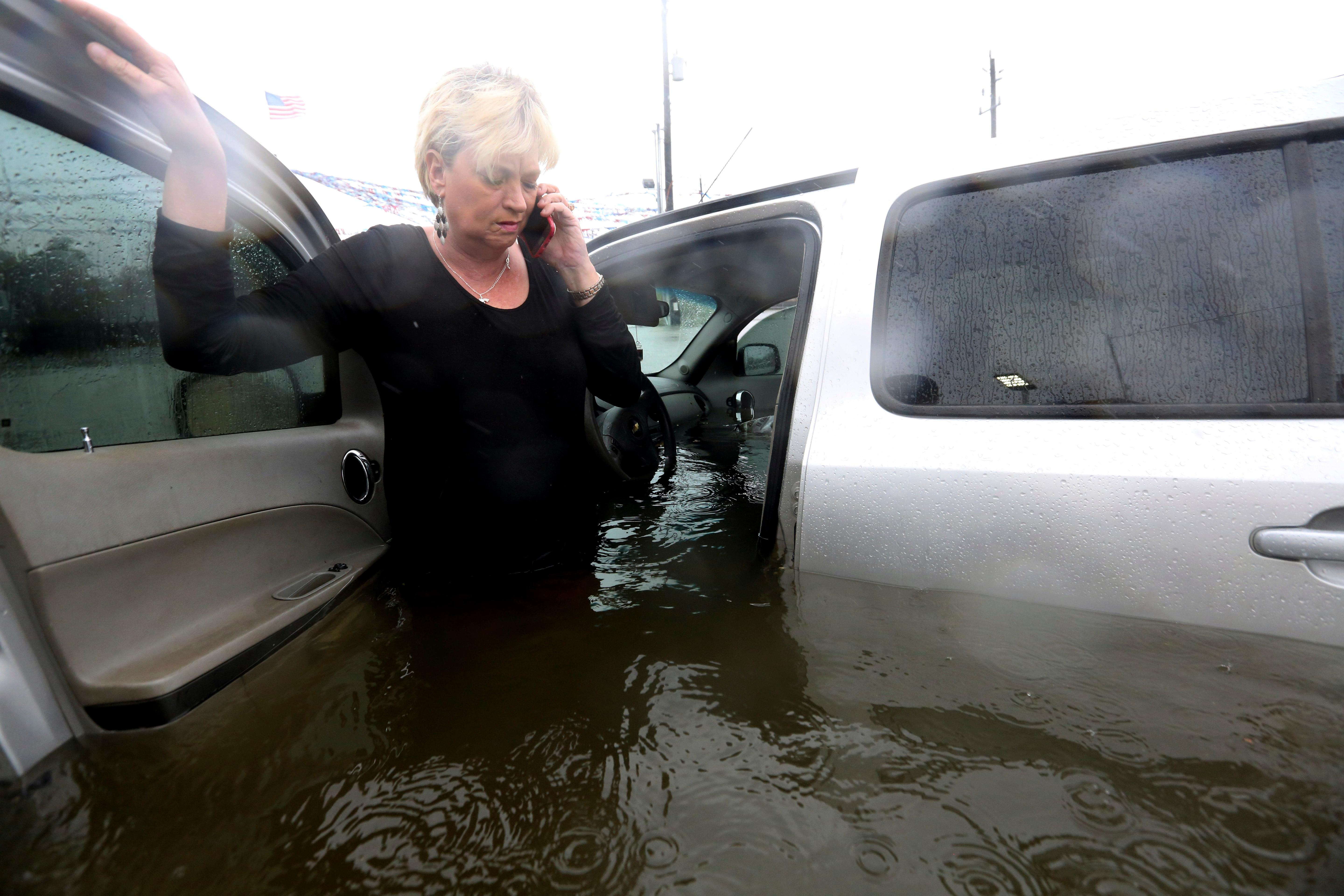 Rhonda Worthington talks on her cell phone with a 911 dispatcher after her car became stuck in rising floodwaters from Tropical Storm Harvey in Houston, Texas, Monday, Aug. 28, 2017. Worthington said she thought the water was low enough to drive through before the vehicle started to float away. (AP Photo/LM Otero)