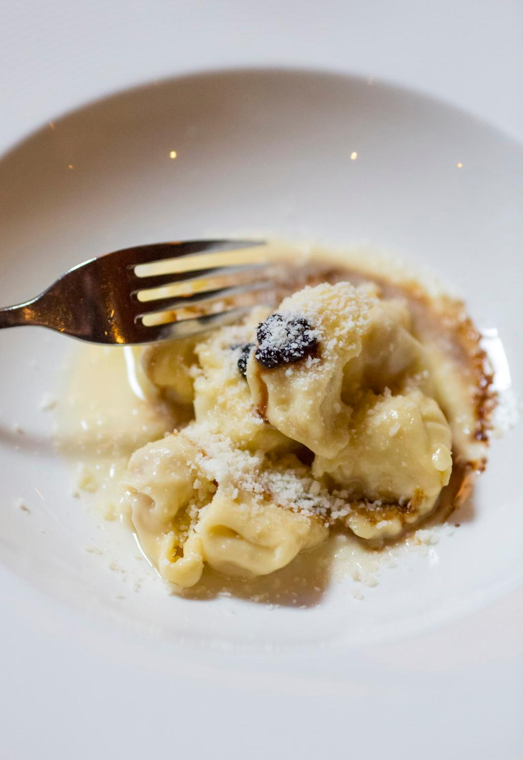 <p>Primo. Cappalletti con Fonduta di Parmigiano – Prosciutto filled cappalletti with Parmigiano fonduta and balsamic pearls (Image: Sy Bean / Seattle Refined).</p>