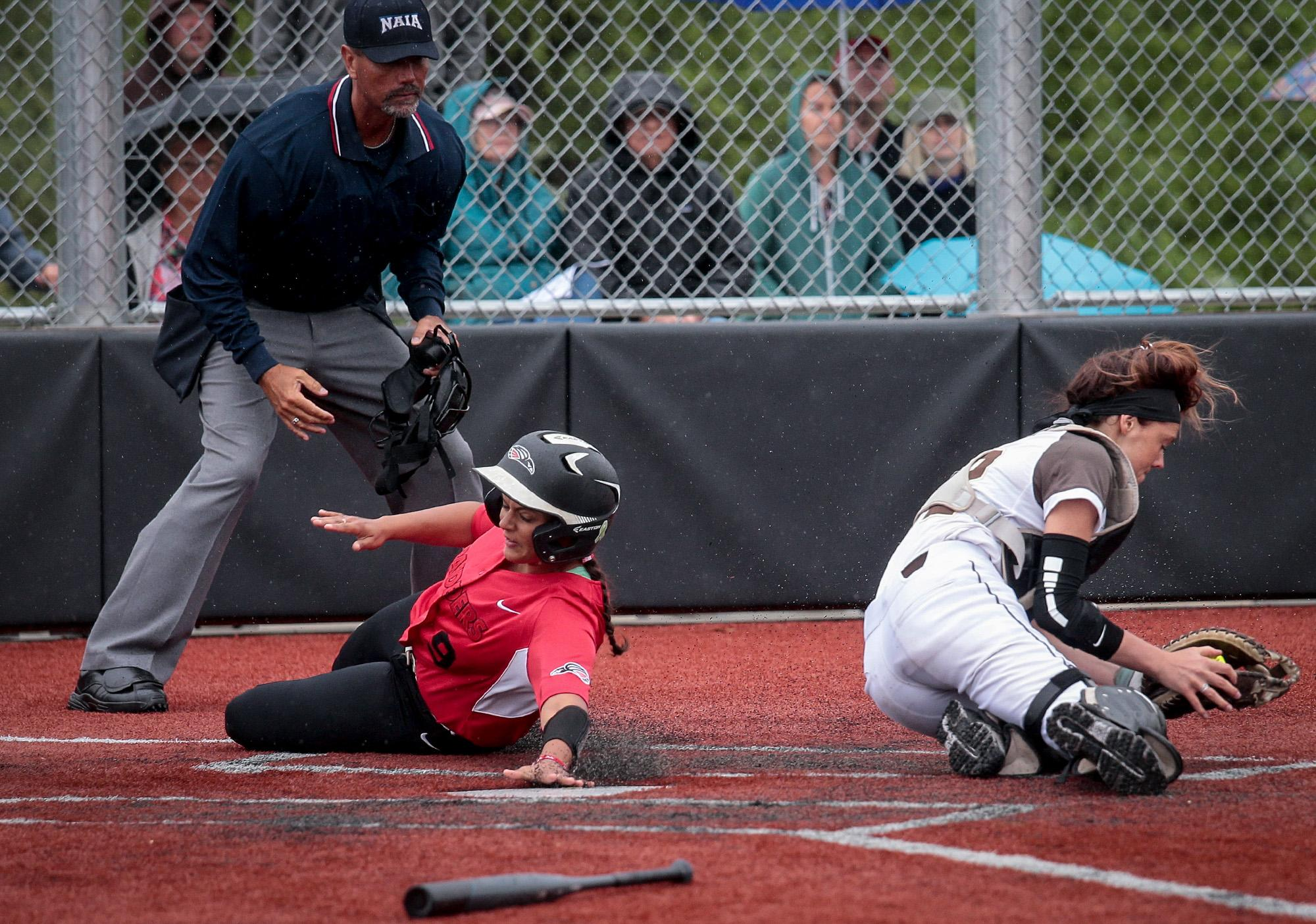 Southern Oregon University senior Davalin Ontiveros slides in under the tag by St. Francis catcher Ally Balandis at US Cellular Community Park on Wednesday.[PHOTO BY:  LARRY STAUTH JR]