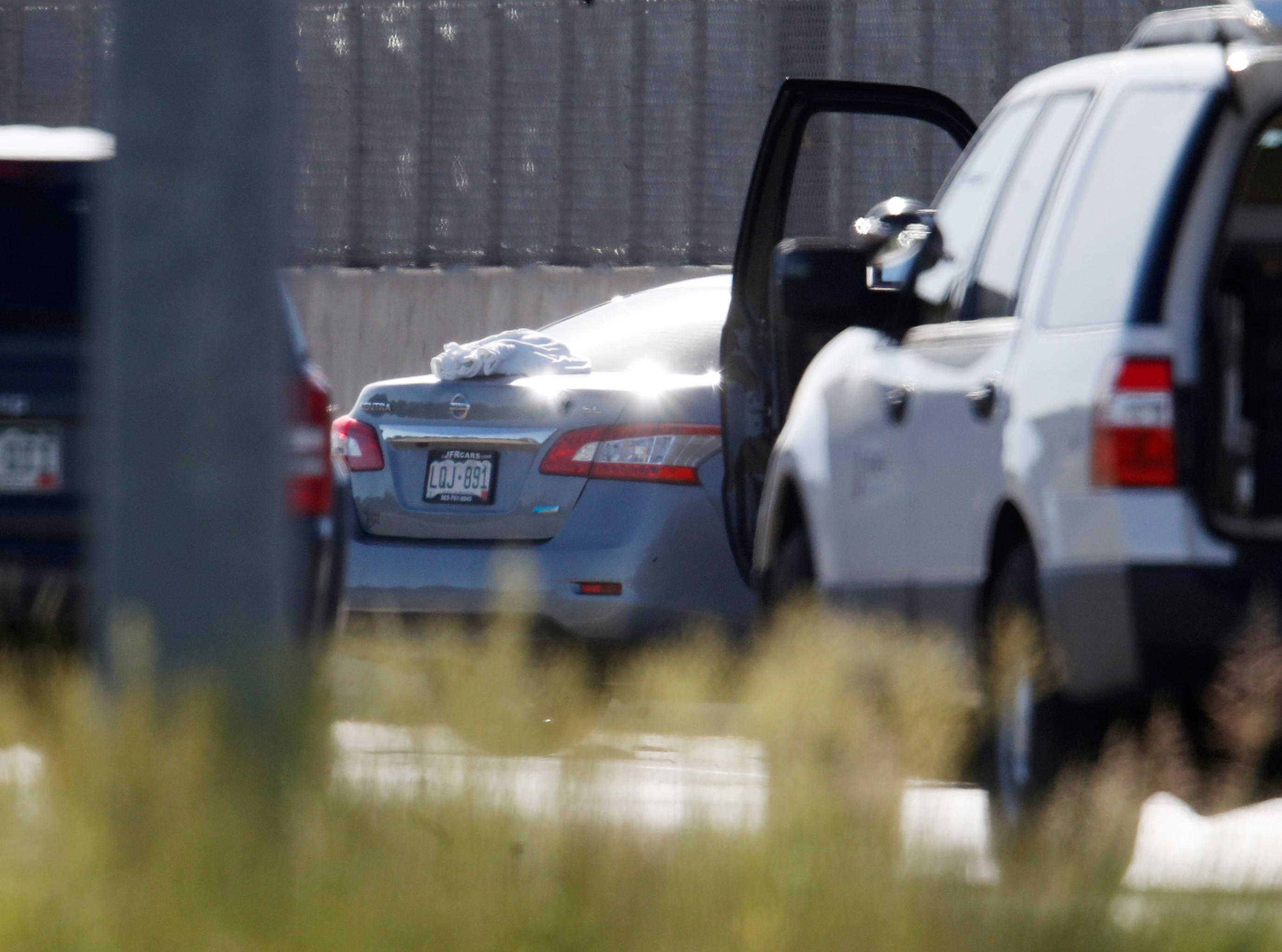 A blanket is shown on the deck of a Nissan sedan, back center, that was being driven by an Uber driver when the vehicle crashed into a retaining wall along Interstate 25 south of downtown Denver early Friday, June 1, 2018. (AP Photo/David Zalubowski)