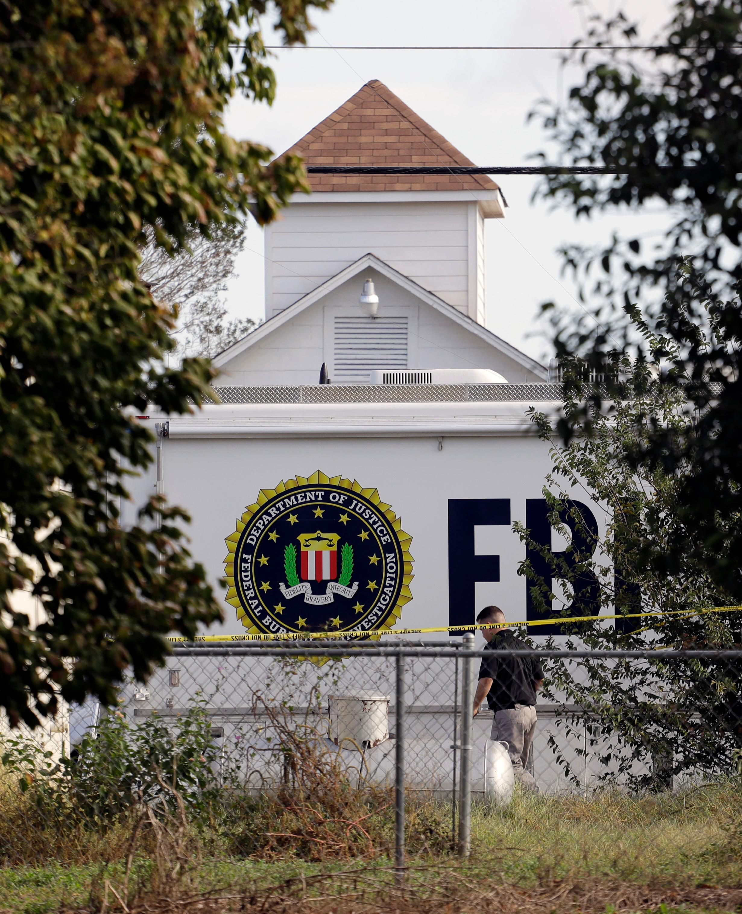 A law enforcement official investigates the scene of a shooting at the First Baptist Church of Sutherland Springs, Monday, Nov. 6, 2017, in Sutherland Springs, Texas. A man opened fire inside the church in the small South Texas community on Sunday, killing and wounding many. (AP Photo/Eric Gay)