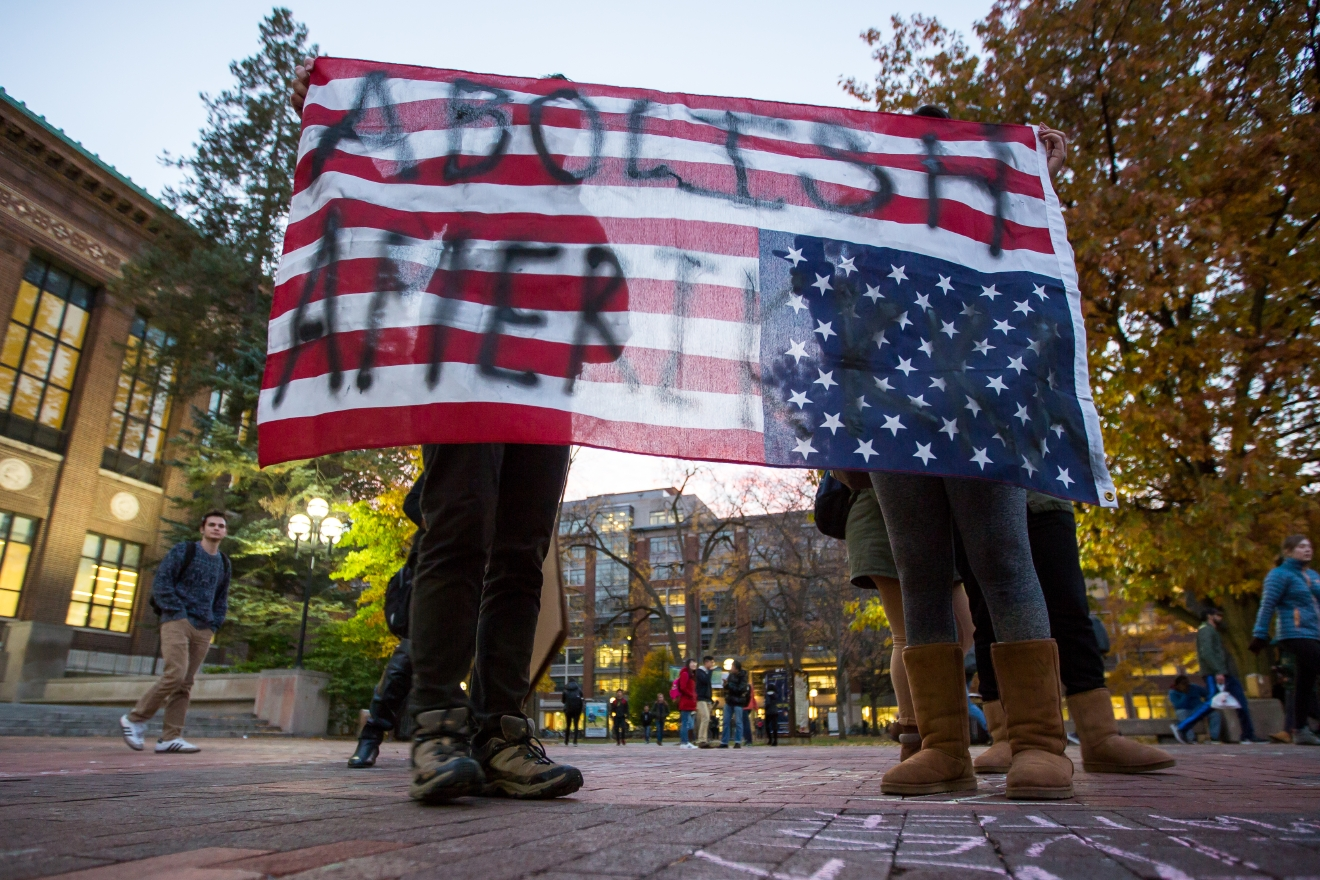 "Two people hold an American Flag upside down, which reads, ""Abolish Amerikkka"" during an anti-Trump rally at the Diag on the University of Michigan's campus on Wednesday, Nov. 9, 2016.  (Matt Weigand/The Ann Arbor News via AP)"