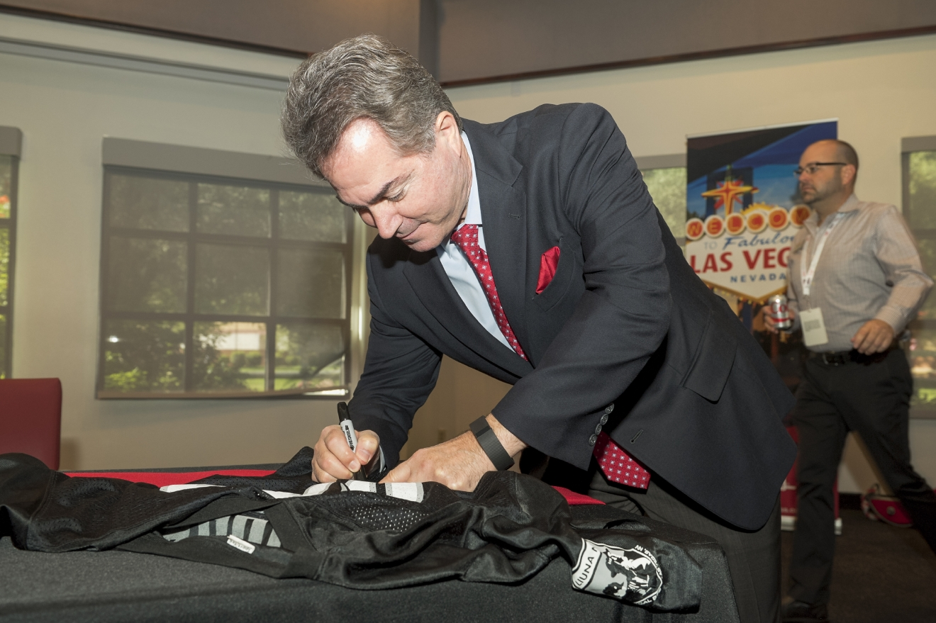 UNLV President Len Jessup signs his name to a Raiders football jersey just before Senate Bill 1 signing ceremony ceremony in UNLV's Tam Alumni Hall on Monday, Oct. 17, 2016. Senate Bill 1 authorizes the funds for the Las Vegas Convention Center District expansion as well as the construction of a 65,000 seat NFL footba'l stadium. (Mark Damon/Las Vegas News Bureau)