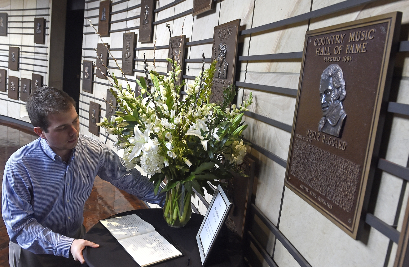 "Ben Hall sets up flowers and a book for condolences in front of the plaque of Merle Haggard in the Rotunda Hall at the Country Music Hall of Fame, Wednesday April 6, 2016, in Nashville, Tenn., after learning of his death. Haggard, who rose from poverty and prison to international fame through his songs about outlaws, underdogs and an abiding sense of national pride in such hits as ""Okie From Muskogee"" and ""Sing Me Back Home,"" died Wednesday at 79, on his birthday. (Larry McCormack/The Tennessean via AP) NO SALES; MANDATORY CREDIT"