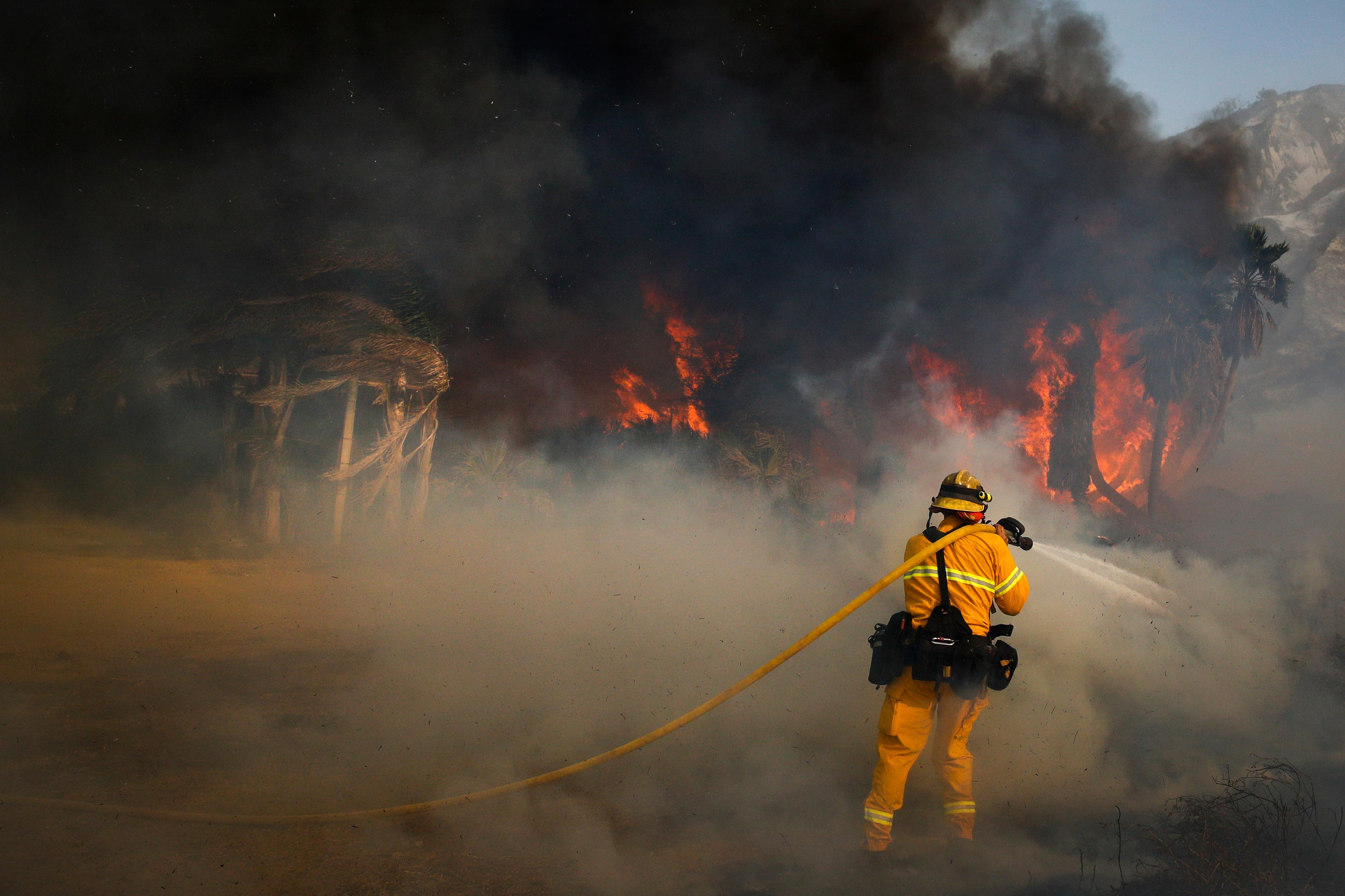 A firefighter battles a wildfire at Faria State Beach in Ventura, Calif., Thursday, Dec. 7, 2017. The wind-swept blazes have forced tens of thousands of evacuations and destroyed dozens of homes. (AP Photo/Jae C. Hong)