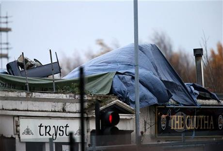 Part of the helicopter tail fin and rotor is seen after the wind has blown off the sheet covering the scene on Saturday, Nov. 30, 2013, following the helicopter crash at the Clutha Bar in Glasgow, Scotland.