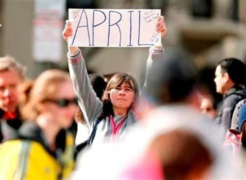 Justine Franco of Montpelier, Vt., holds up a sign near Copley Square in Boston looking for her missing friend, April, who was running in her first Boston Marathon Monday, April 15, 2013.