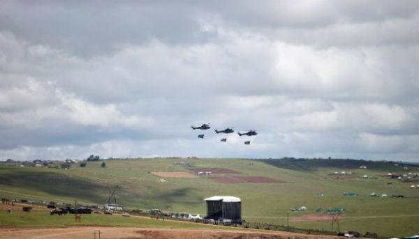 Three helicopters fly over the grave site of former South African President Nelson Mandela as his family lays his body to rest in his hometown of Qunu, South Africa, on Sunday December 15.