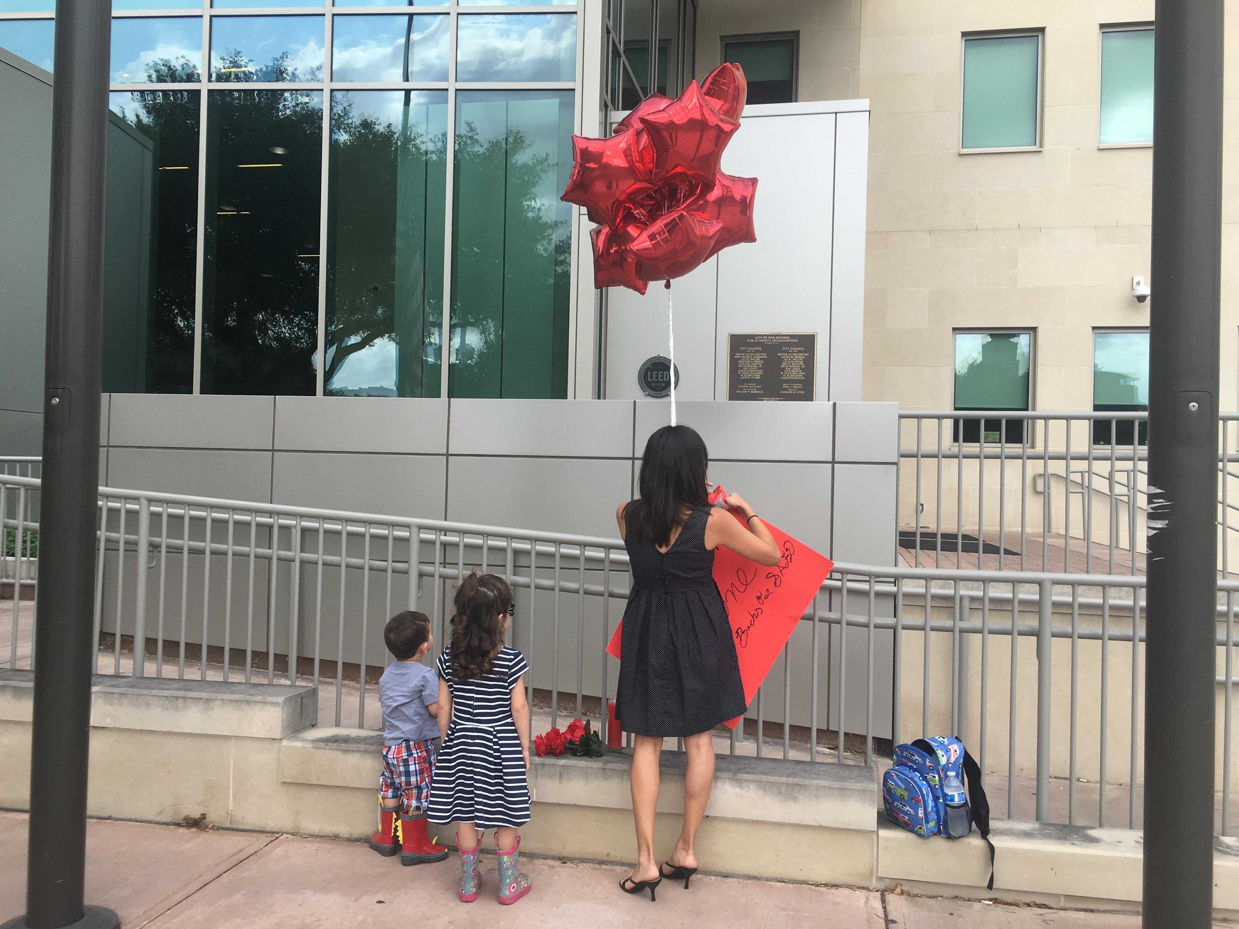 A family posts a memorial up outside Public Safety Headquarters on Friday morning in honor of San Antonio Firefighter Scott Deem, who lost his life in a fire on Thursday night. (SBG San Antonio)