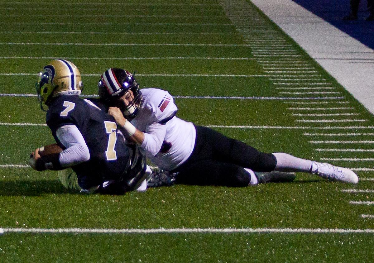 A Thurston defender pulls Marist quarterback Reow Jackson (#7) to the ground just before the end zone. The Marist Spartans defeated the Thurston Colts 17 to 14. Photo by Ben Lonergan, Oregon News Lab