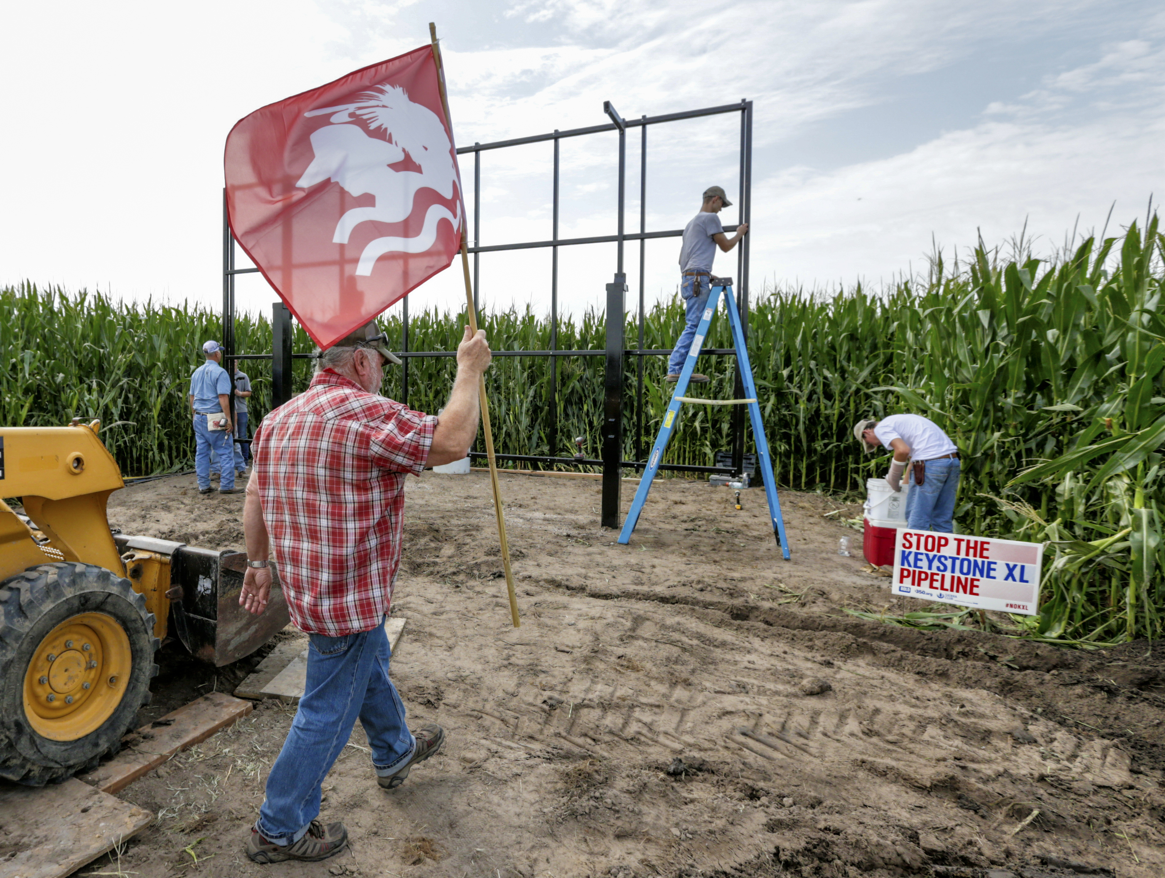 In this July 29, 2017 photo, activist Tom Genung of the organization Bold Nebraska is about to pitch a flag of the Cowboy Indian Alliance at the proposed path of the Keystone XL pipeline, in Silver Creek, Neb., where landowner Jim Carlson and activists were building solar panels. Despite new uncertainty over whether TransCanada, the builder of the Keystone XL pipeline will continue the project, longtime opponents in Nebraska aren't letting their guard down and neither are law enforcement officials who may have to react to protests if it wins approval. (AP Photo/Nati Harnik)