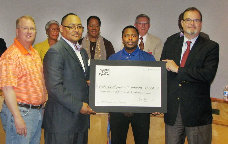 <p>In this Monday April 18, 2016 photo provided by the Roanoke-Chowan News-Herald, the Rev. Anthony Rawlings, left, and Christian Martin, third from left, of Creek Development Corporation accept a $7,500 grant from Bruce McKay, right, representing the Atlantic Coast Pipeline Community Investment Program during a regularly scheduled meeting of the Northampton County Board of Commissioners in Jackson, N.C. (Keith Hoggard/Roanoke-Chowan News-Herald via AP)</p>