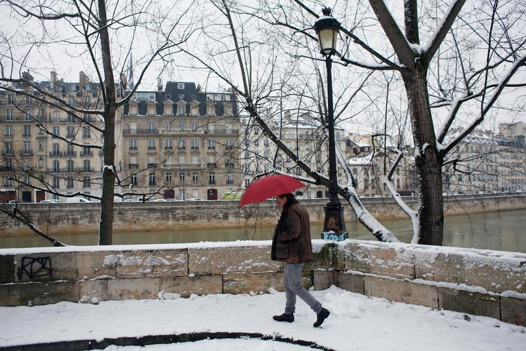 A man walks in a snowy street of Paris, Friday, Feb. 9, 2018. Authorities are telling drivers in the Paris region to stay home as snow and freezing rain have hit a swath of France ill-prepared for the wintry weather. (AP Photo/Thibault Camus)