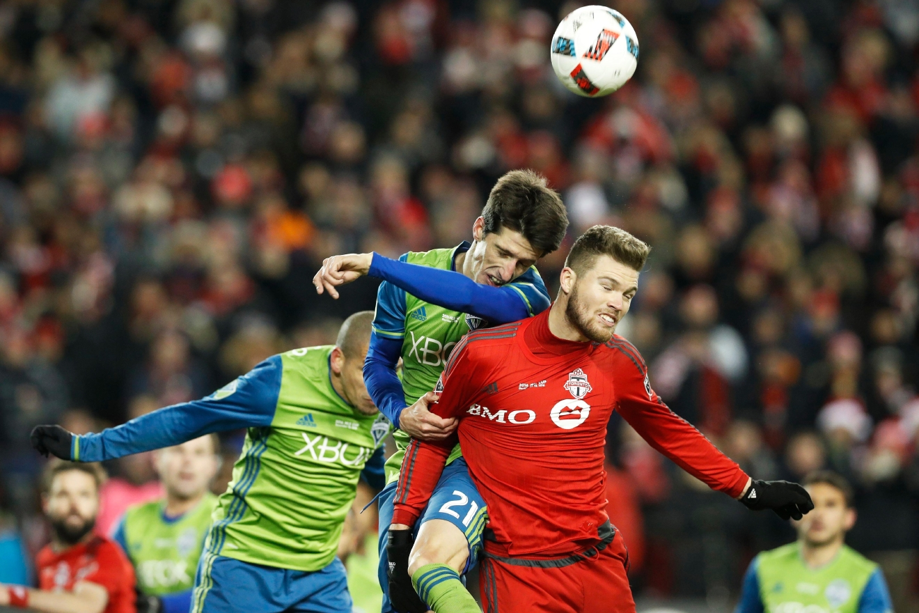 Seattle Sounders midfielder Alvaro Fernandez (21) and Toronto FC forward Eriq Zavaleta (15) jump to head the ball during second-half MLS Cup final soccer action in Toronto, Saturday, Dec. 10, 2016. (Mark Blinch/The Canadian Press via AP)