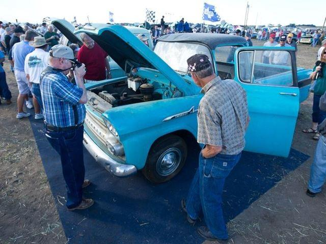 Potential bidders check out a 1958 Chevrolet Cameo pickup. The pickup has just over one mile on it.