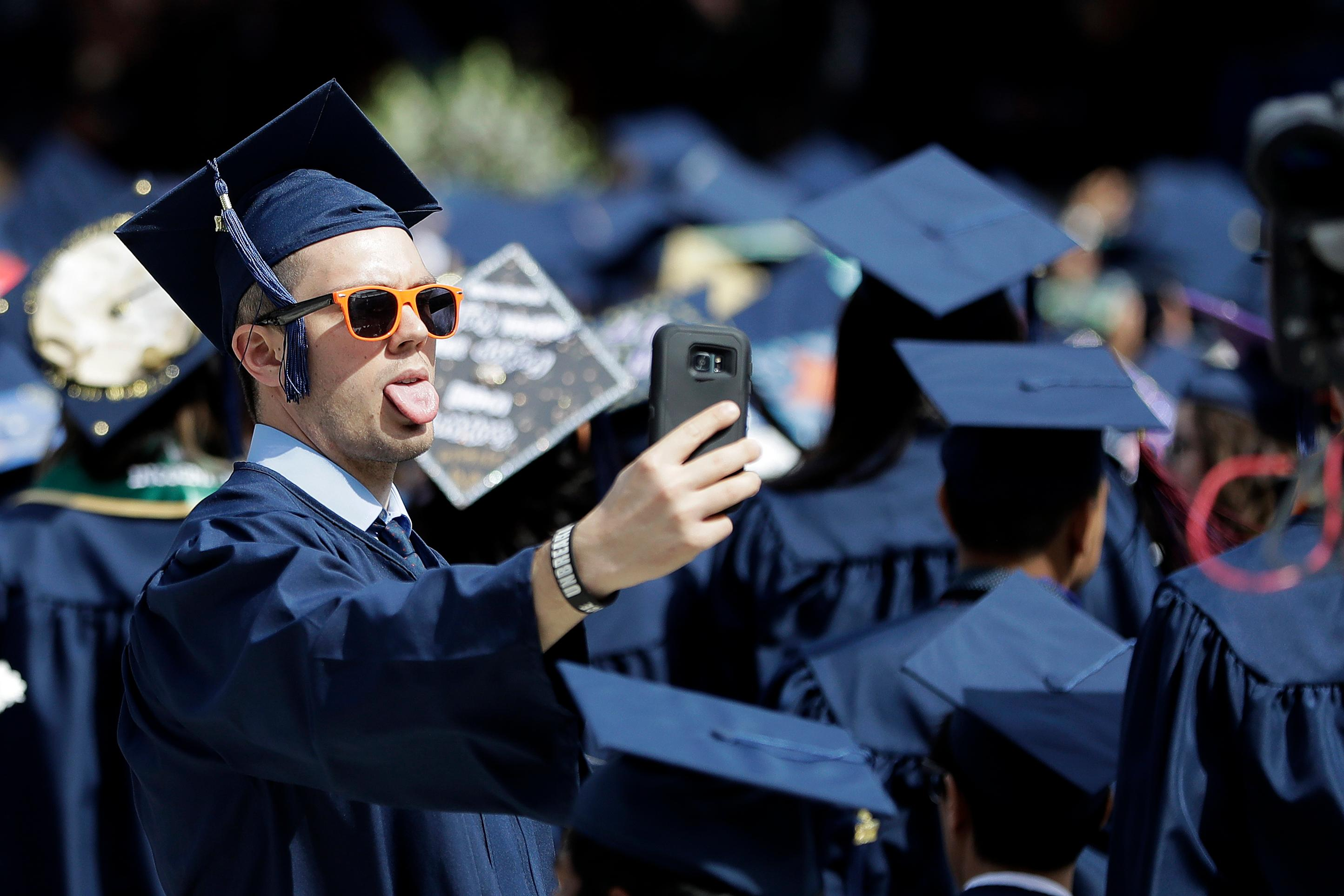 A graduate takes a selfie as musical group Bon Jovi performs during a surprise appearance at the Fairleigh Dickinson University commencement ceremony, Tuesday, May 16, 2017, at MetLife Stadium in East Rutherford, N.J. (AP Photo/Julio Cortez)