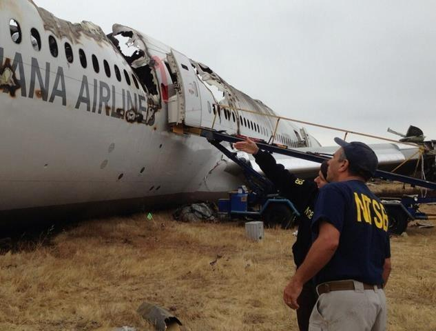 Investigators look at the side of the plane.