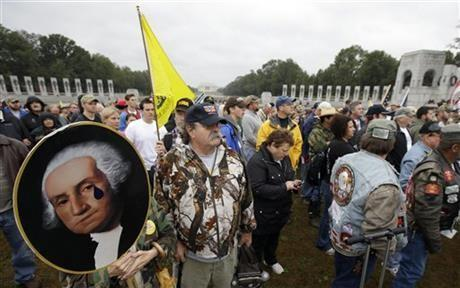 Noreen Grimm stands next to her husband David Grimm, both from Pittsburgh, Pa., holding a portrait of President George Washington during a rally at the World War II Memorial in Washington Sunday, Oct. 13, 2013.