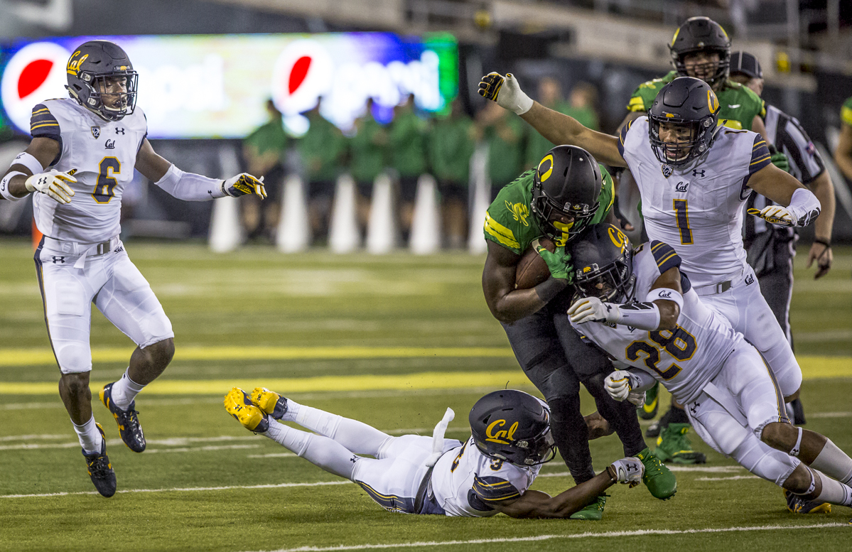 Oregon running back Royce Freeman (#21) attempts to dodge a tackle from California center back Elijah Hicks (#3). The Oregon Ducks lead the California Golden Bears 17 to 7 at the end of the first half at Autzen Stadium in Eugene, Ore. Photo by Ben Lonergan, Oregon News Lab