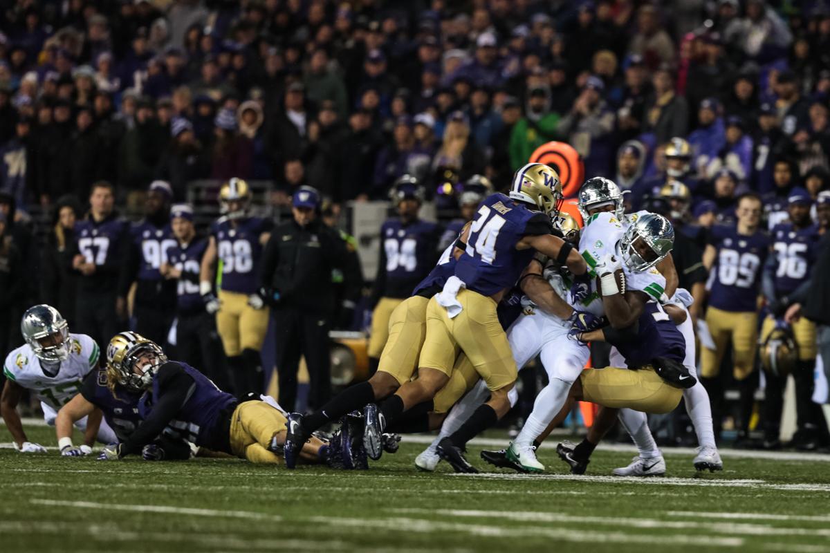 Oregon running back Royce Freeman (#21) is tackled by a trio of Washington defenders. The Oregon Ducks are trailing the Washington Huskies 3 - 17 at halftime.  The Huskies rallied with a 17-point second quarter after a slow first quarter on a cold and rainy night in Seattle, Washington.  Photo by Austin Hicks, Oregon News Lab