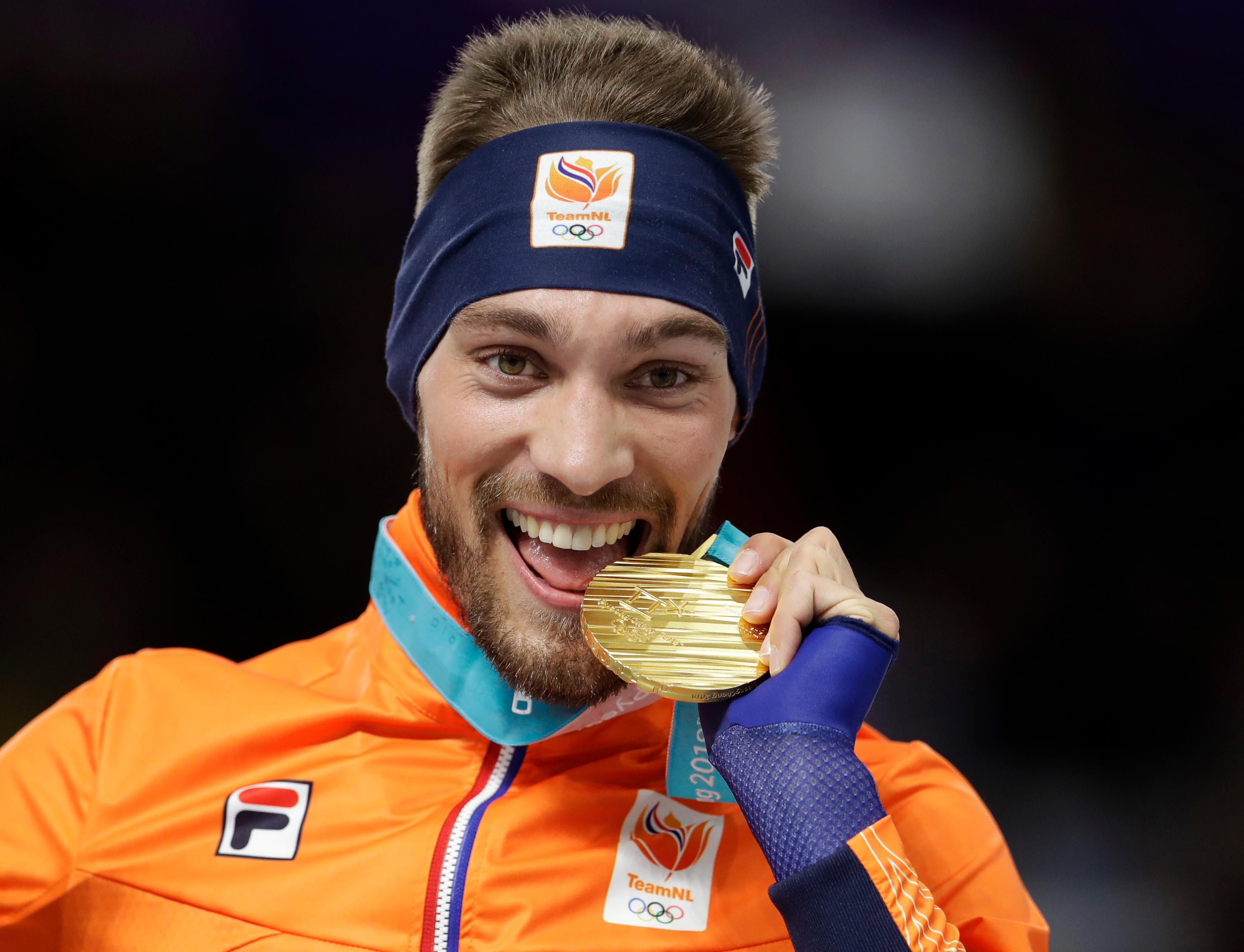 Gold medalist Kjeld Nuis of The Netherlands celebrates on the podium after the men's 1,000 meters speedskating race at the Gangneung Oval at the 2018 Winter Olympics in Gangneung, South Korea, Friday, Feb. 23, 2018. (AP Photo/Petr David Josek)