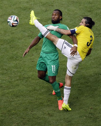 Ivory Coast's Didier Drogba fights for the ball with Colombia's Mario Yepes during the group C World Cup soccer match between Colombia and Ivory Coast at the Estadio Nacional in Brasilia, Brazil, Thursday, June 19, 2014.