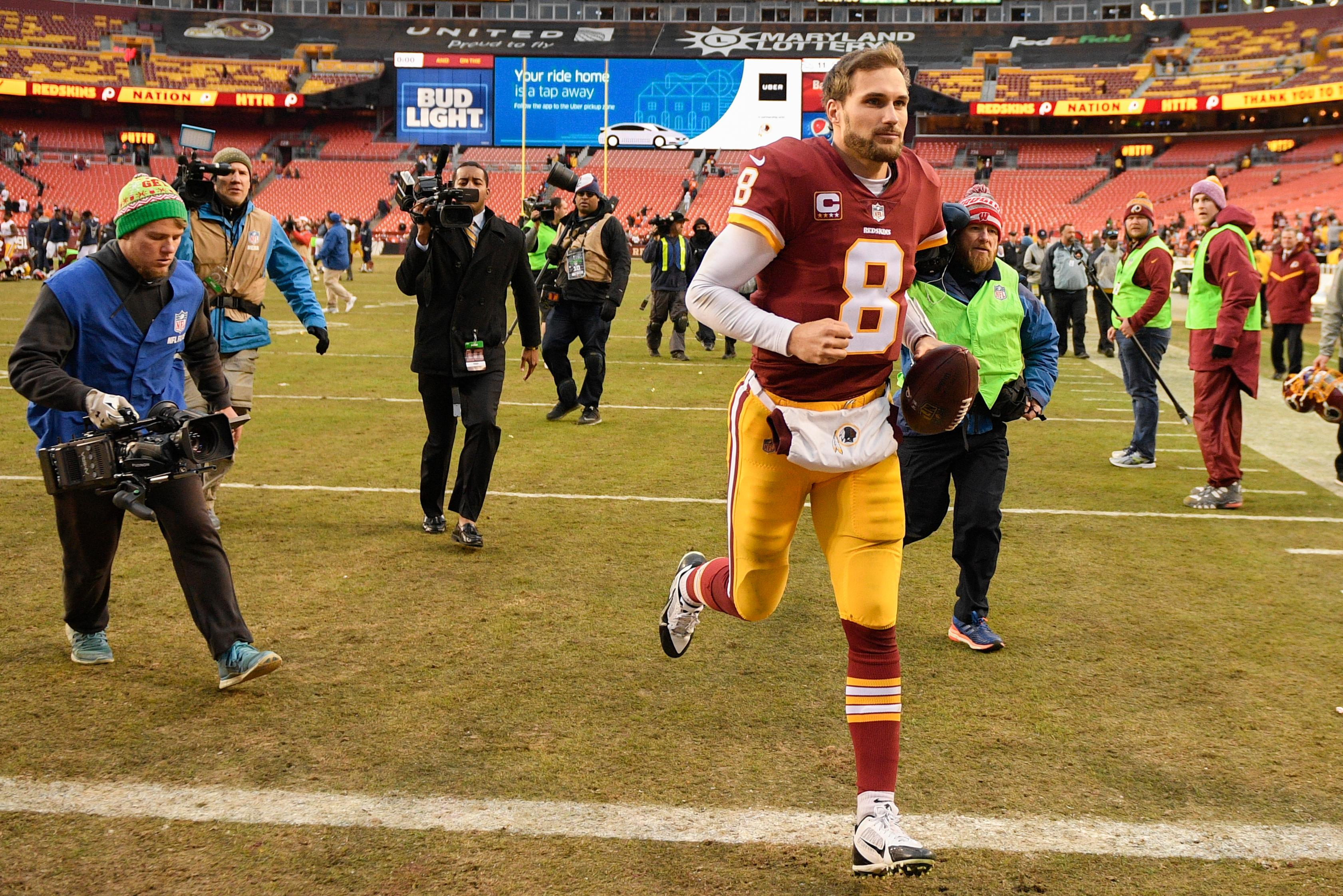 Washington Redskins quarterback Kirk Cousins (8) runs off the field after an NFL football game against the Denver Broncos in Landover, Md., Sunday, Dec 24, 2017. The Redskins defeated the Broncos 27-11. (AP Photo/Nick Wass)