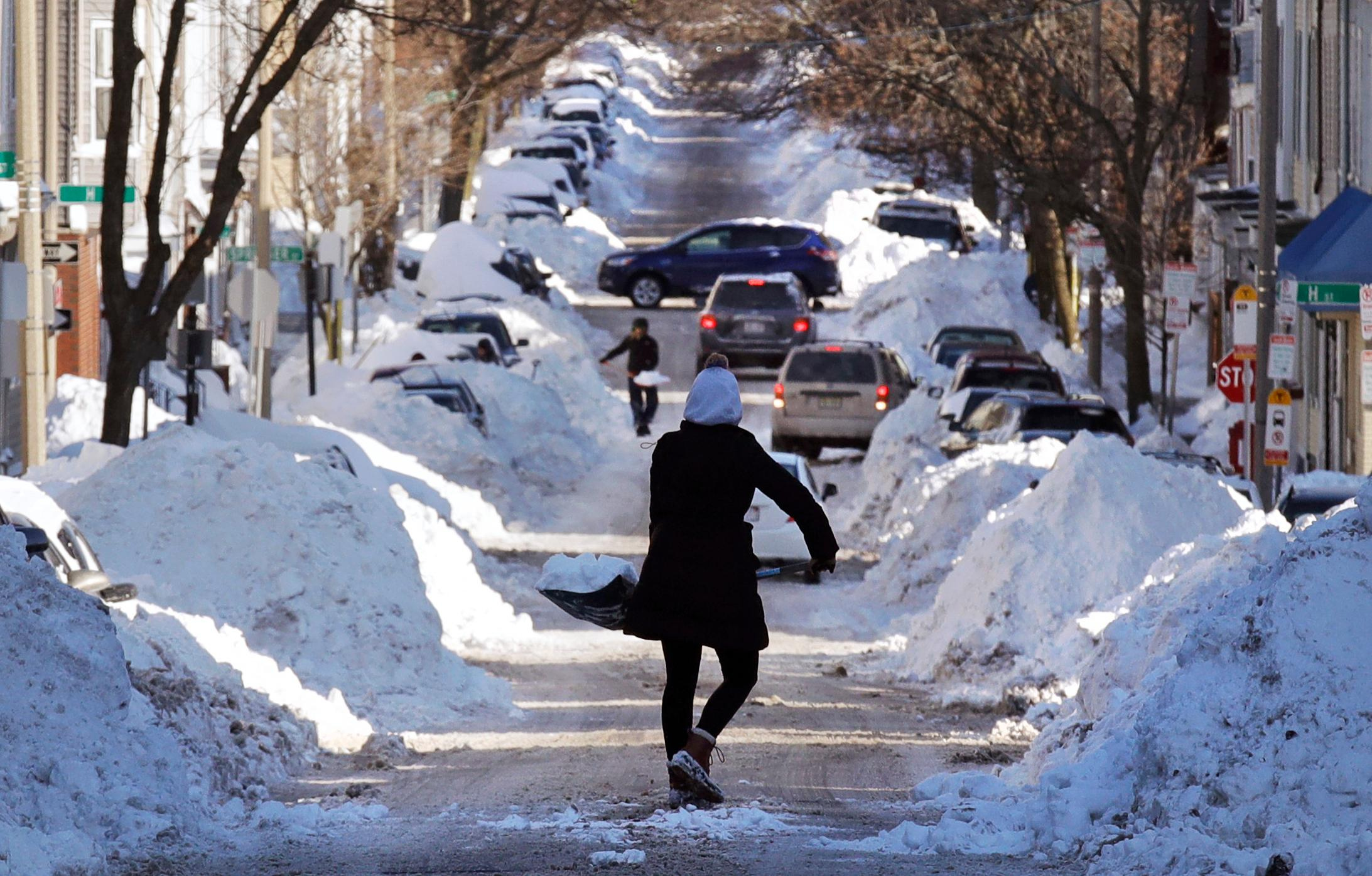 Mollie Lane carries a shovel-full of snow down the street to a pile while digging her car out in the South Boston neighborhood of Boston, Friday, Jan. 5, 2018. Frigid temperatures, some that could feel as cold as minus 30 degrees, moved across the East Coast on Friday as the region attempted to clean up from a massive winter storm. (AP Photo/Charles Krupa)