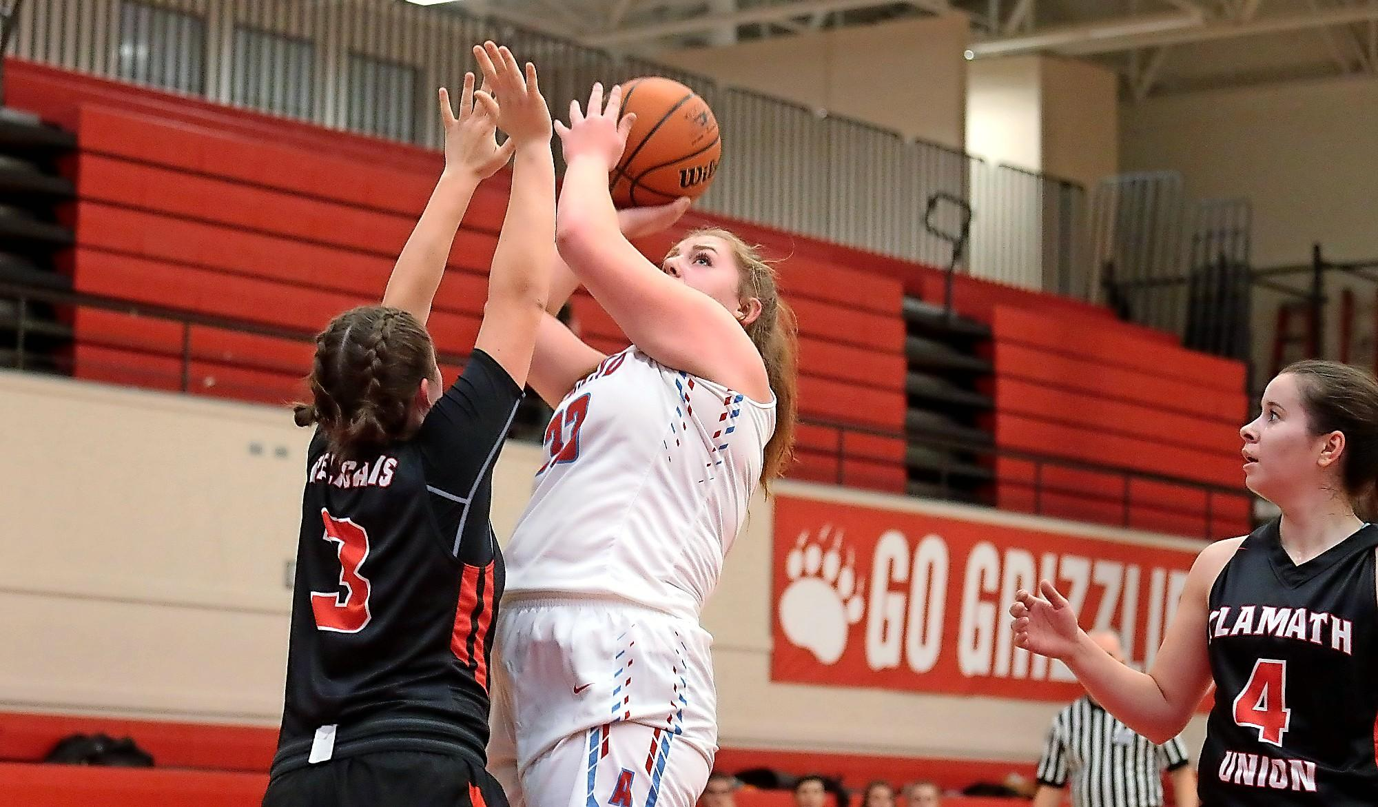 Ashland High sophomore Kendyl Abel attempting to shoot over the reach of Klamath Union defender Mercedes Charkins at Mountain Avenue Gym on Wednesday.(PHOTO BY:  LARRY STAUTH JR)