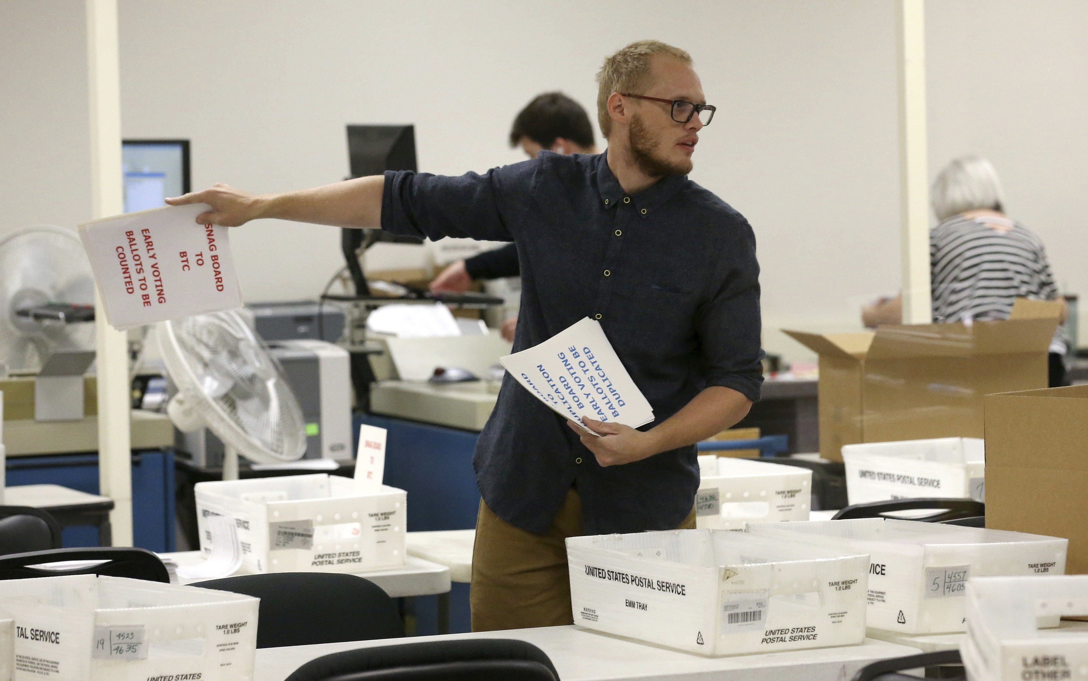 A worker prepares volunteers to verify ballots at the Maricopa County Recorder's Office Thursday, Nov. 8, 2018, in Phoenix. (AP Photo/Ross D. Franklin)