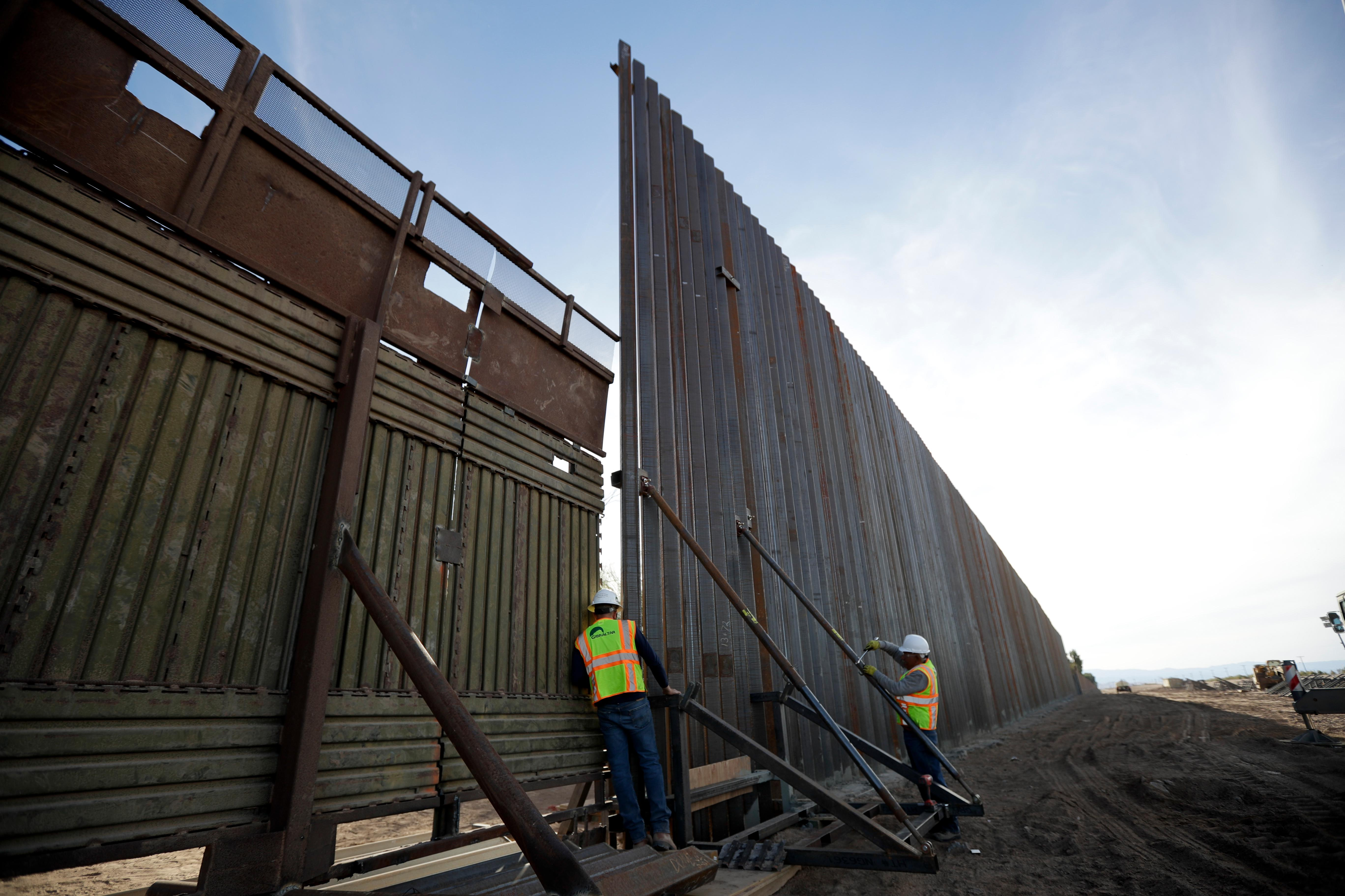 In this March 5, 2018, photo, a worker looks between the first section of a newly-constructed structure along the border separating Mexicali, Mexico and Calexico, Calif. As Donald Trump prepares for his first visit to the U.S.-Mexico border as president, little has changed despite the heated rhetoric. (AP Photo/Gregory Bull)