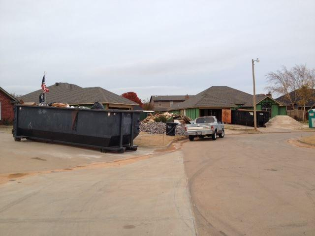 A dumpster sits in a driveway outside a Moore home as the rebuilding process continues.